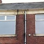 A guttering downpipe with water damage behind